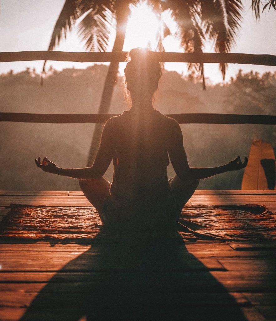 chica meditando durante el atardecer