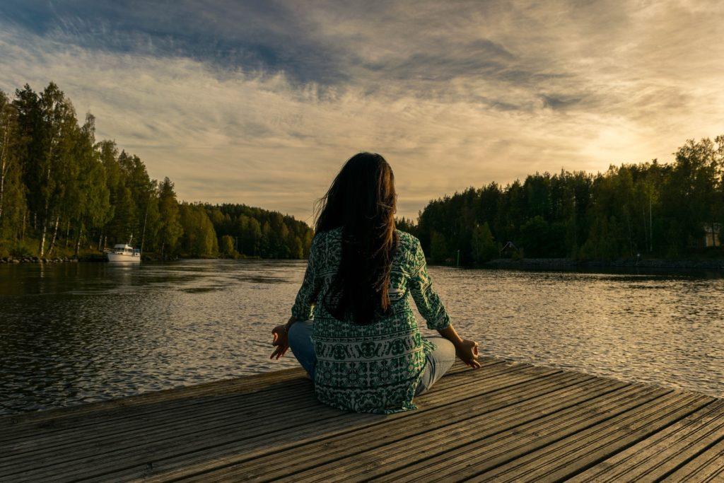 chica meditando delante de un lago