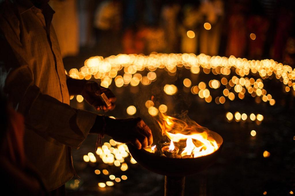hombre encendiendo velas durante el diwali