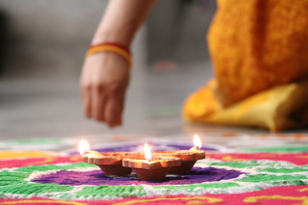 mujer preparando decoración rangoli durante diwali en la India